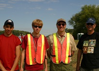 Four men standing posing for a photo, two of them wearing orange safety vests