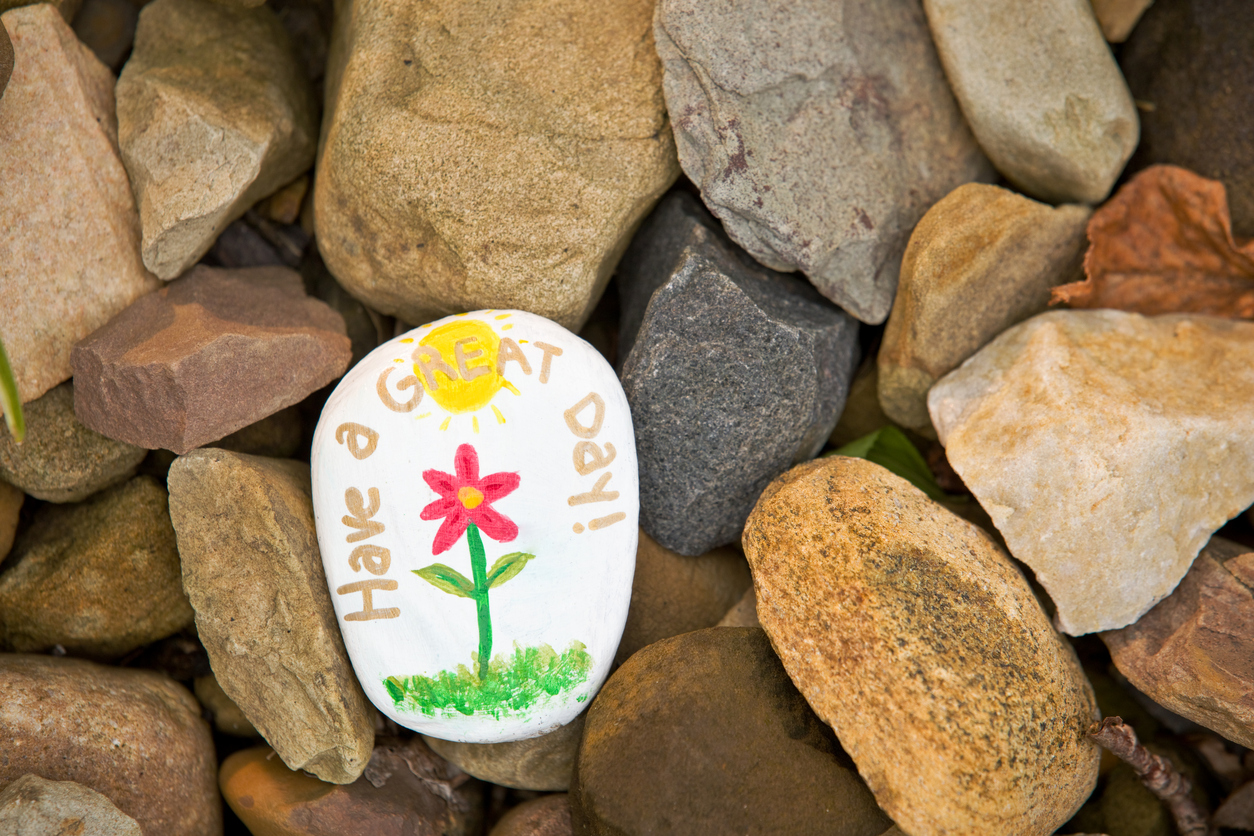 A painted white rock with text that reads Have a great day! sitting on a bed of more rocks
